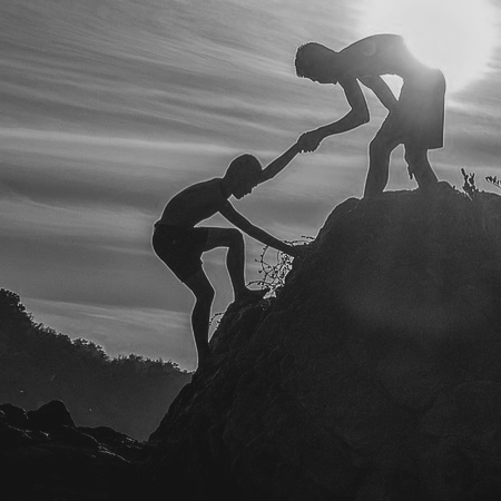 Boy helping another climb a hill